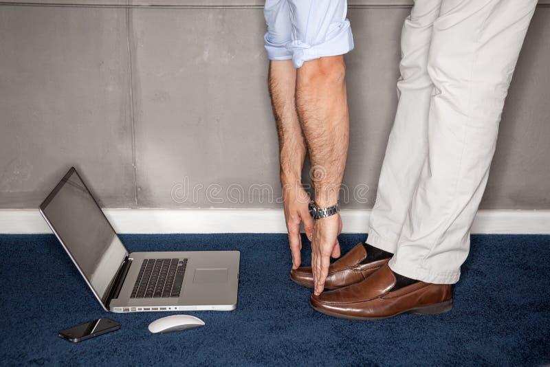 Équipez la position dans le bureau faisant des exercices avec l'ordinateur portatif image libre de droits