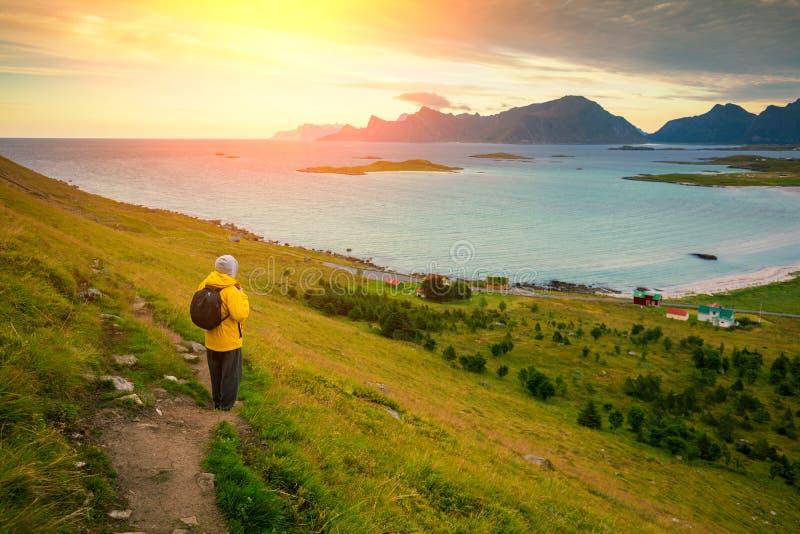 Équipez la position de touristes sur une montagne et un coucher du soleil de regarder au-dessus du fjord photographie stock