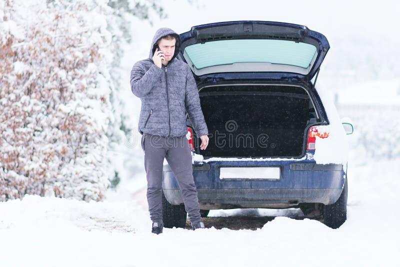 Équipez la position devant la voiture endommagée et appeler des services de voiture à photographie stock libre de droits