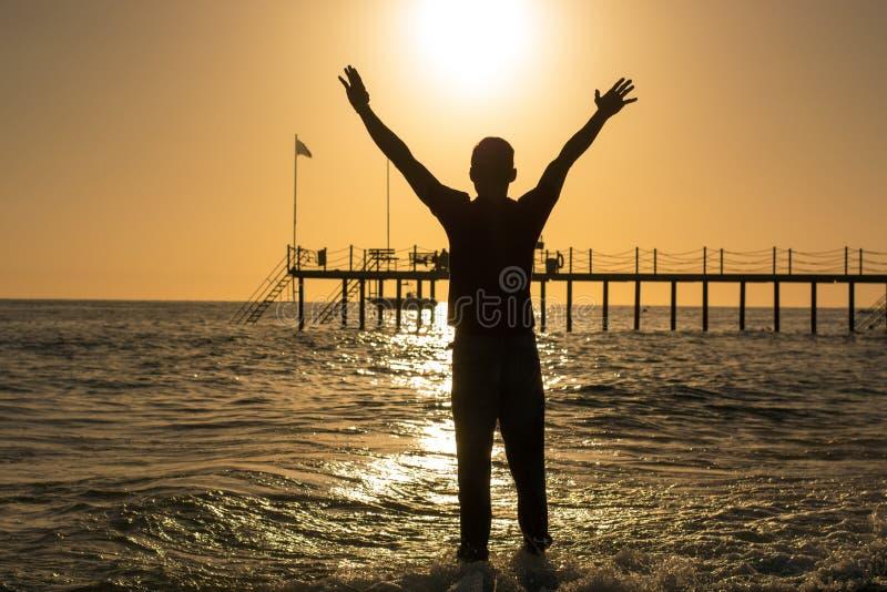Équipez la position sur la plage, soulevant ses mains au-dessus de sa tête à t photo libre de droits