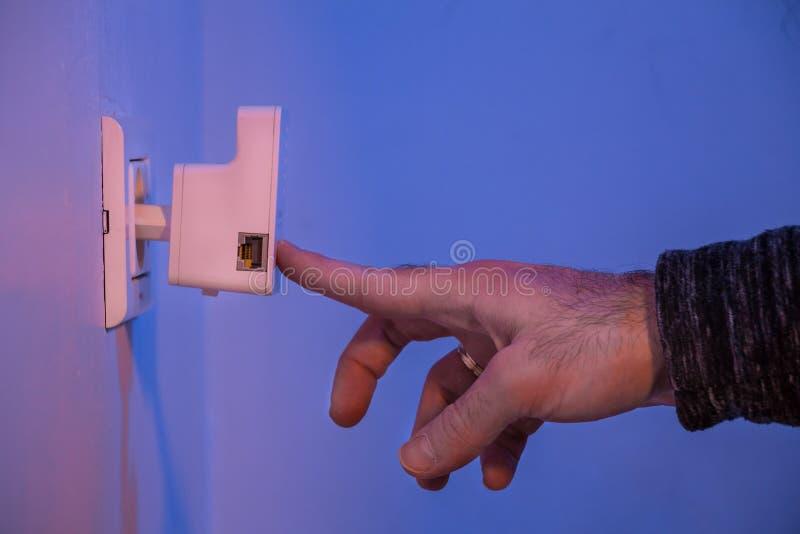 Équipez la presse avec son doigt sur le bouton de WPS sur le répétiteur de WiFi qui I images stock