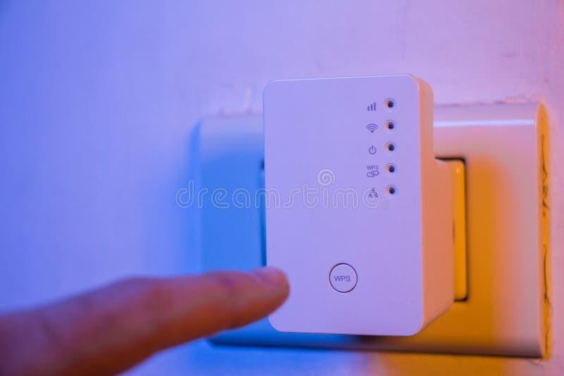 Équipez la presse avec son doigt sur le bouton de WPS sur le répétiteur de WiFi qui I photo stock