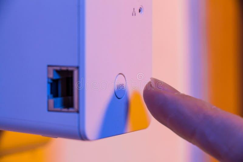 Équipez la presse avec son doigt sur le bouton de WPS sur le répétiteur de WiFi qui I photographie stock libre de droits