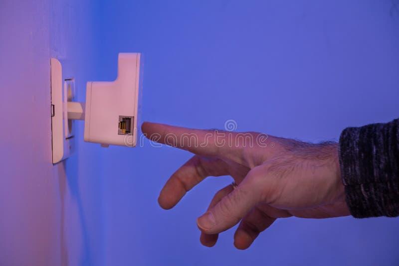 Équipez la presse avec son doigt sur le bouton de WPS sur le répétiteur de WiFi qui I photo libre de droits