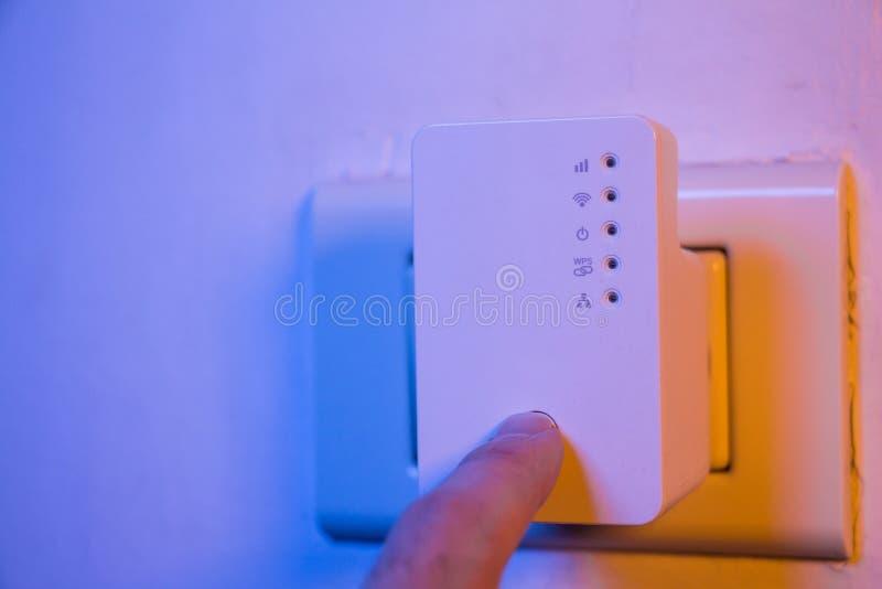 Équipez la presse avec son doigt sur le bouton de WPS sur le répétiteur de WiFi qui I images libres de droits