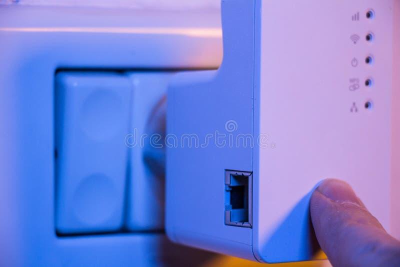 Équipez la presse avec son doigt sur le bouton de WPS sur le répétiteur de WiFi qui I photographie stock