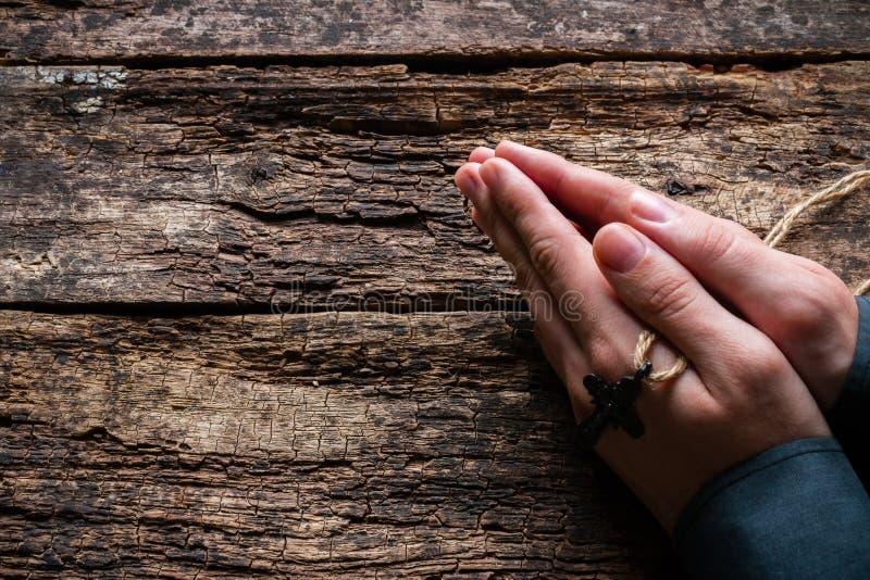 Équipez la prière avec une croix dans des ses mains photos stock