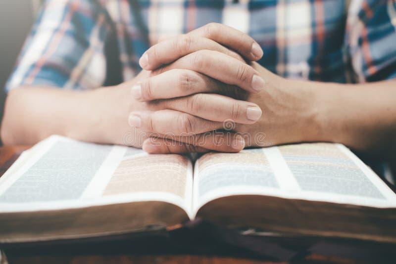 Équipez la prière, mains étreintes ensemble sur sa bible image libre de droits