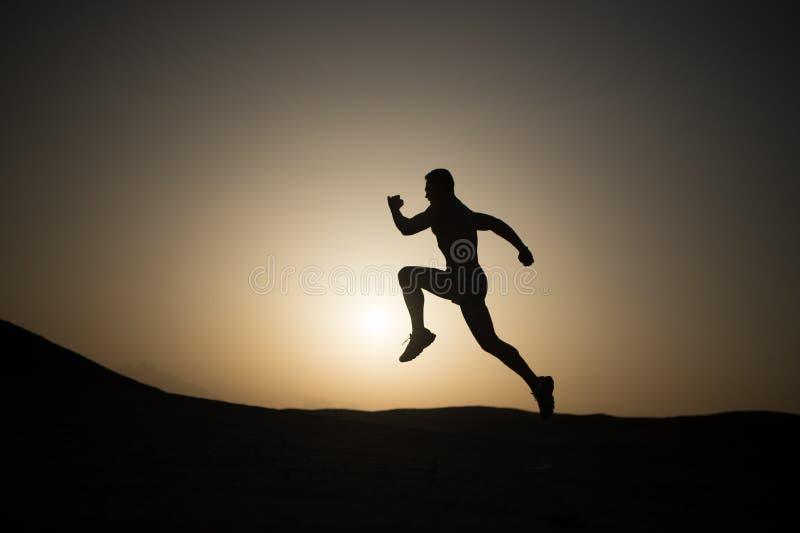 Équipez la silhouette courante au coucher du soleil, jeune Caucasien couru en montagne photos libres de droits