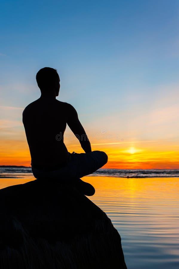 Équipez la silhouette se reposant sur la pierre au bord de la mer contemplant le soleil photographie stock