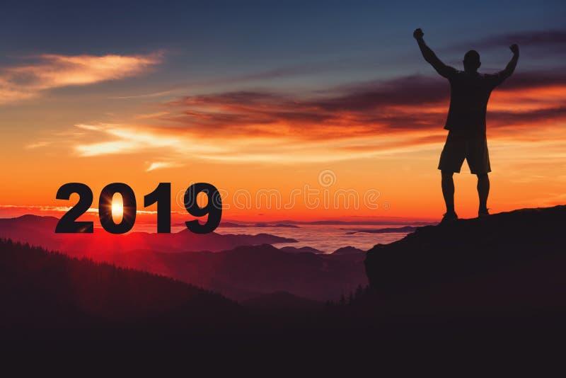 Équipez la silhouette sur le dessus de montagne observant le lever de soleil et le 2018 photos libres de droits