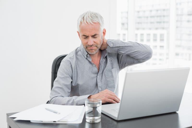 Équipez la souffrance du mal de cou tout en à l'aide de l'ordinateur portable au bureau images libres de droits