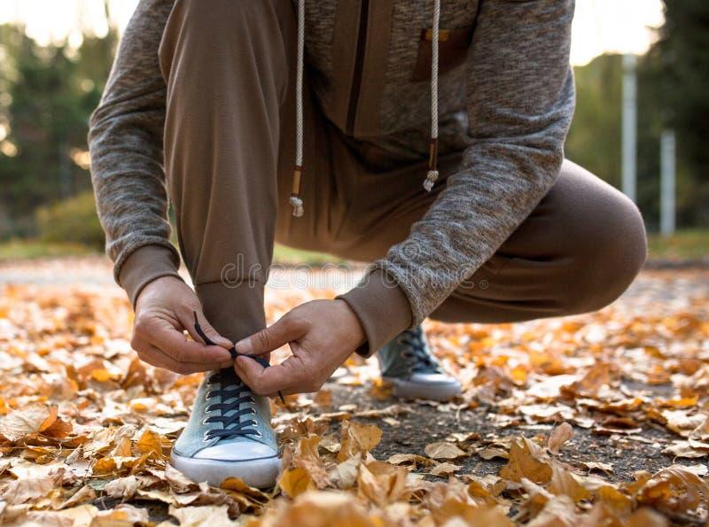 Équipez lacer ses chaussures folâtres étant prêtes pour pulser en parc d'atumn photo libre de droits