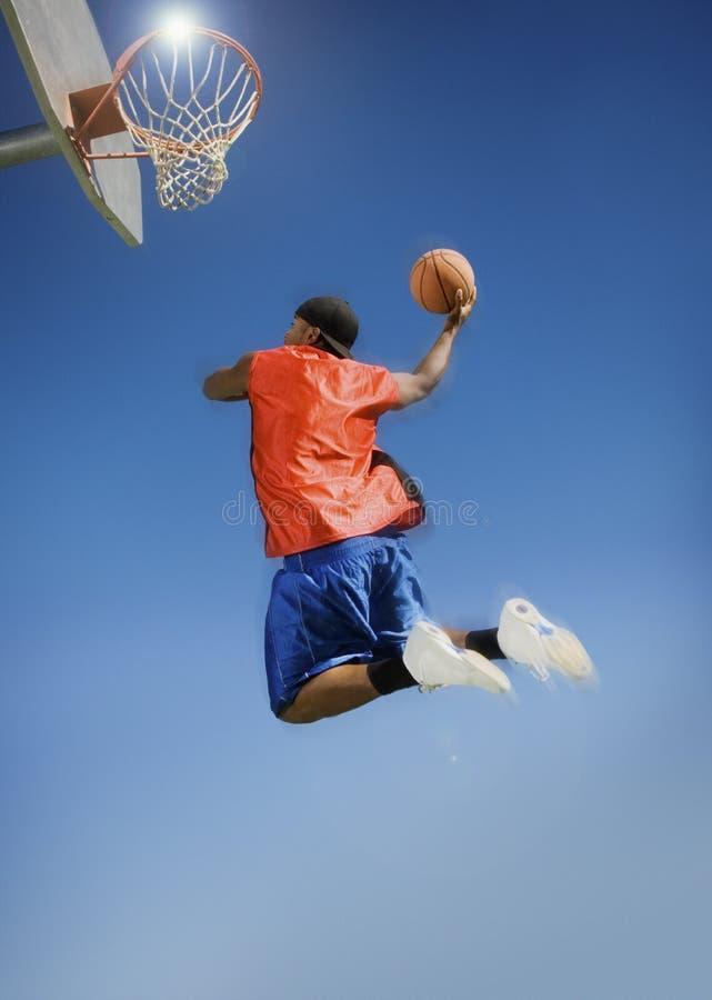 Équipez le basket-ball trempant dans le cercle contre le ciel bleu photos stock