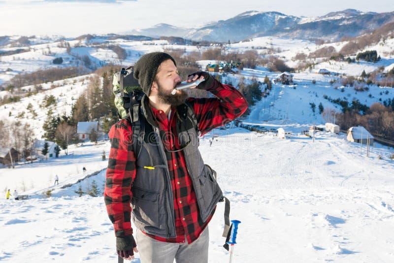 Équipez le boire d'un flacon de hanche sur la montagne neigeuse images stock