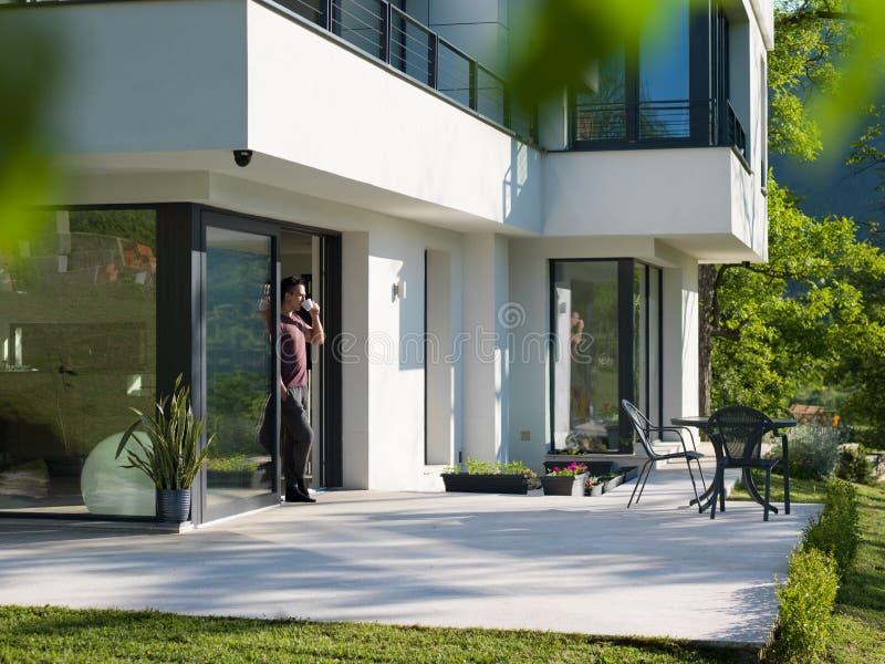 Équipez le café potable devant sa villa à la maison de luxe photo stock