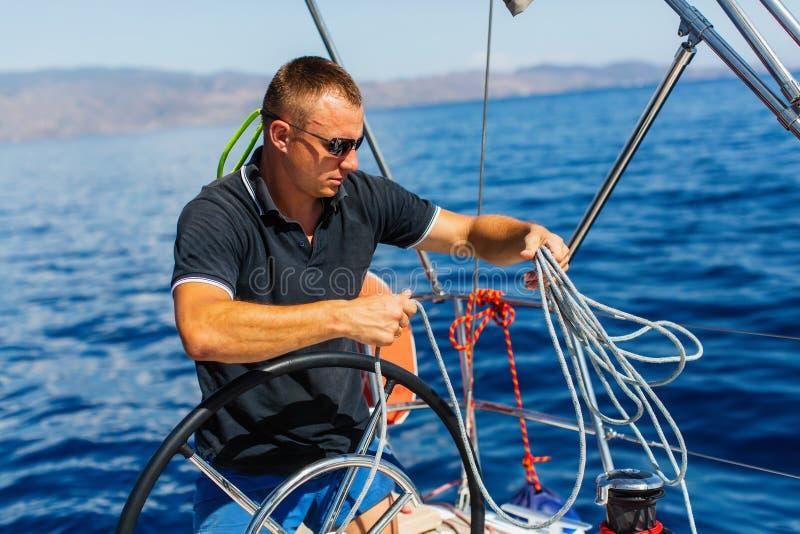 Équipez le capitaine aux contrôles de barre d'un yacht de navigation sport photos stock