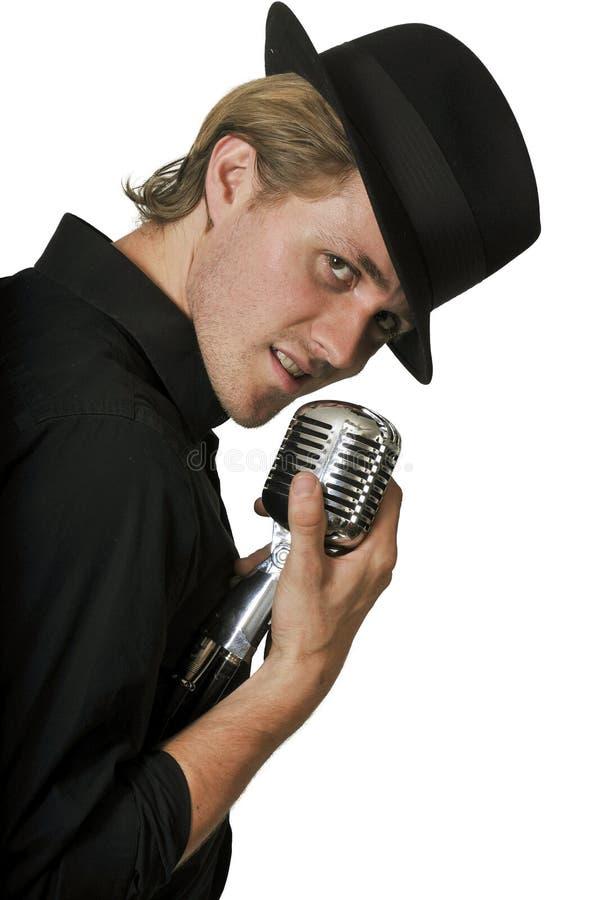 Équipez le chant dans le microphone photo stock