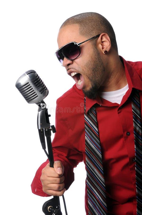 Équipez le chant dans le microphone de cru photos stock