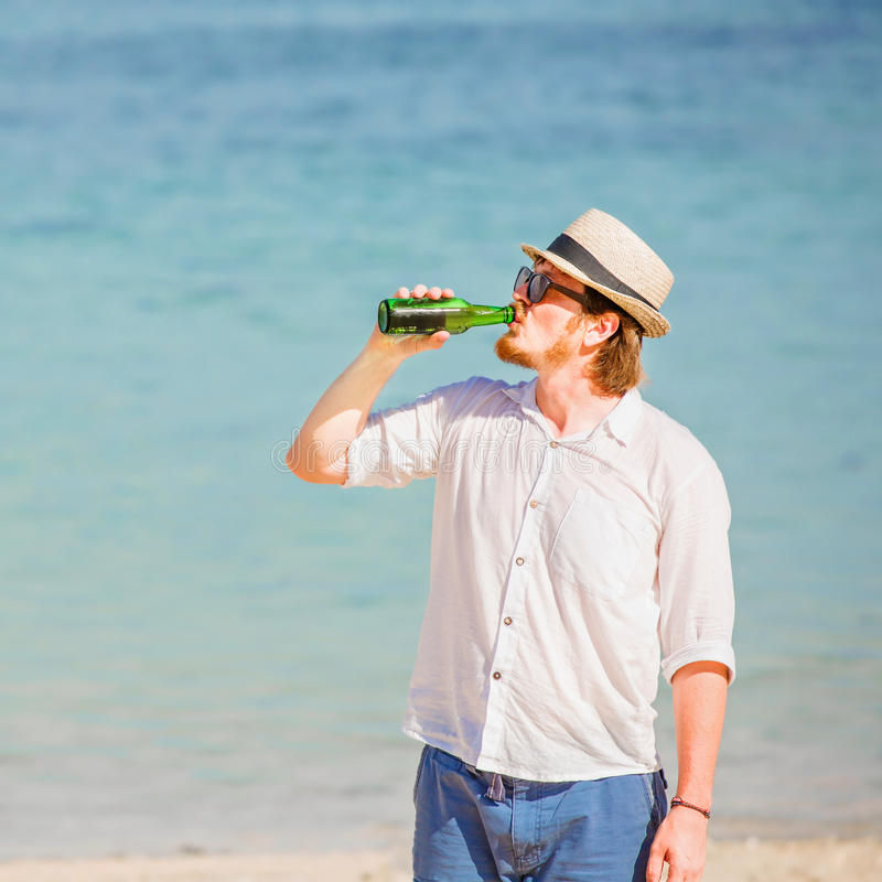 Équipez le chapeau et les lunettes de soleil de port enjoing la bière dans a photos stock