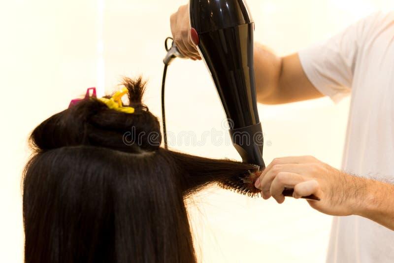 Équipez le coiffeur employant le ventilateur pour sécher des cheveux de client image libre de droits