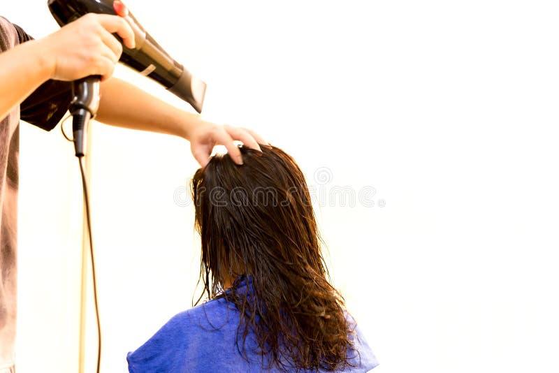 Équipez le coiffeur employant le ventilateur pour sécher des cheveux de client images stock