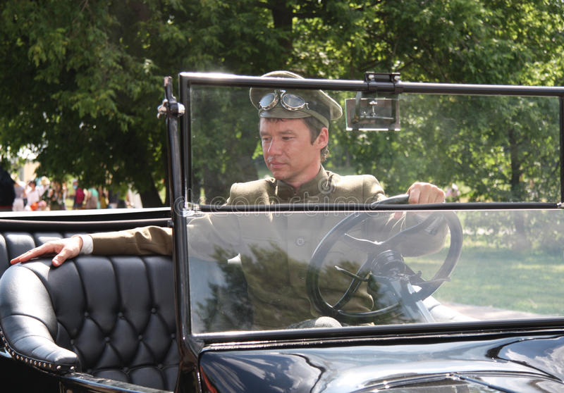 Équipez le conducteur dans une rétro voiture convertible luxueuse image libre de droits