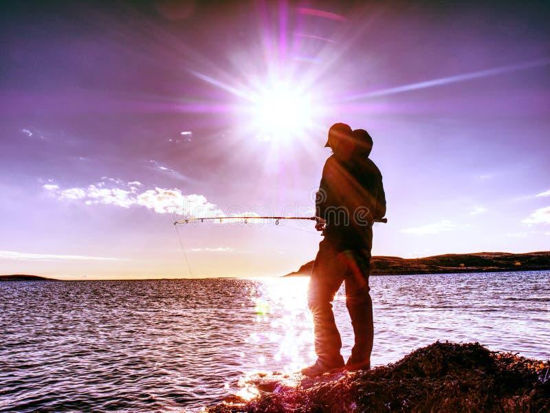 Équipez le contrôle poussant l'amorce et les jets il loin dans la mer Pêcheur avec la canne à pêche photos stock