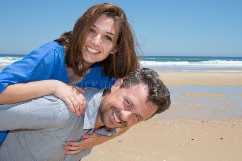 équipez le ferroutage de couples de femme étreignant sur une plage images stock
