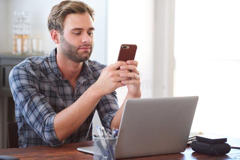 Équipez le flirt à son téléphone tout en se reposant à son bureau photo stock