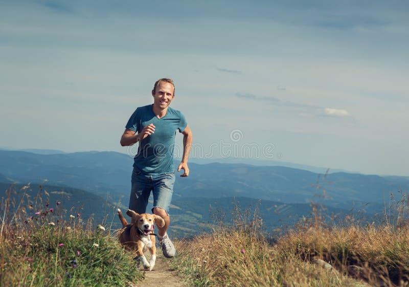 Équipez le fonctionnement avec son chien sur le plateau de montagne image libre de droits