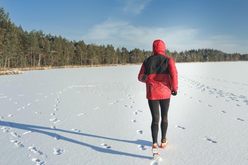 Équipez le fonctionnement dehors sur la bâche de neige en nature d'hiver photographie stock libre de droits