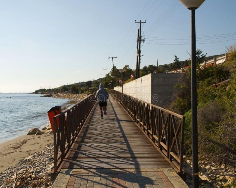 Équipez le fonctionnement sur l'allée de littoral au coucher du soleil photographie stock libre de droits