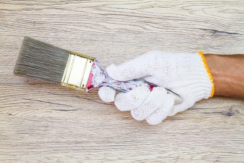 Équipez le gant blanc de port de main du ` s tenant le vieux pinceau grunge dessus image stock