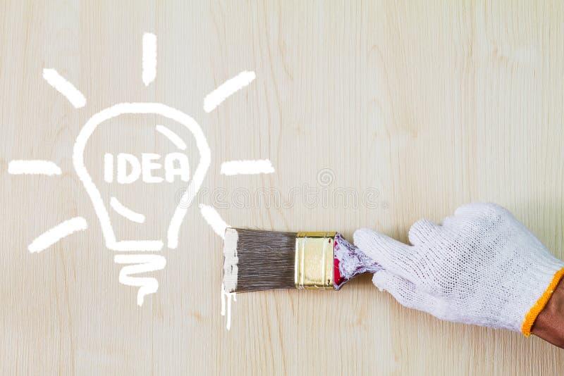 Équipez le gant blanc de port de main du ` s tenant le vieux pinceau grunge et peignant l'ampoule sur le mur en bois photo stock