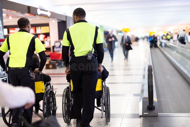 Équipez le gardien poussant les personnes âgées dans le fauteuil roulant dans l'aéroport images stock