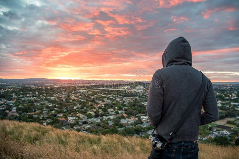 Équipez le lever de soleil de observation hoody de port au-dessus de la ville d'Auckland images libres de droits
