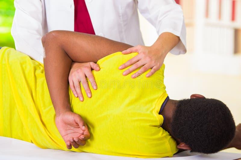 Équipez le mensonge en descendant le traitement physique d'épaule du physio- thérapeute, patient regardant dans l'appareil-photo  photographie stock