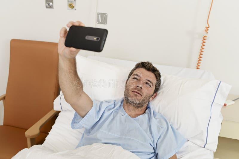 Équipez le mensonge sur la clinique d'hôpital de lit tenant le téléphone portable prenant à photo de selfie d'autoportrait déprim photos libres de droits