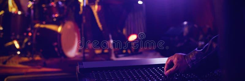 Équipez le mixeur son fonctionnant avec des interprètes sur l'étape lumineuse dans la boîte de nuit image stock