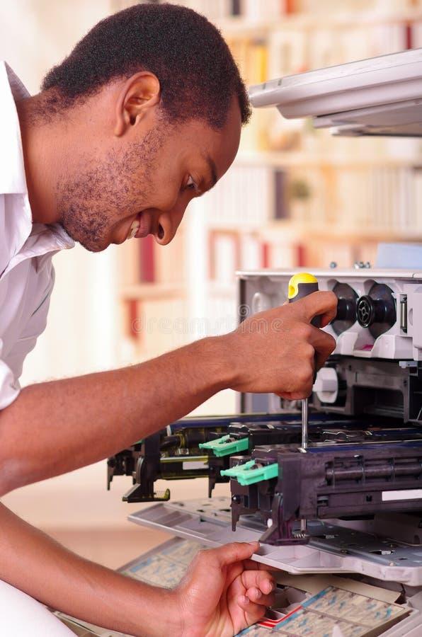 Équipez le penchement au-dessus du photocopieur ouvert pendant les réparations d'entretien utilisant l'outil tenu dans la main, p photos libres de droits