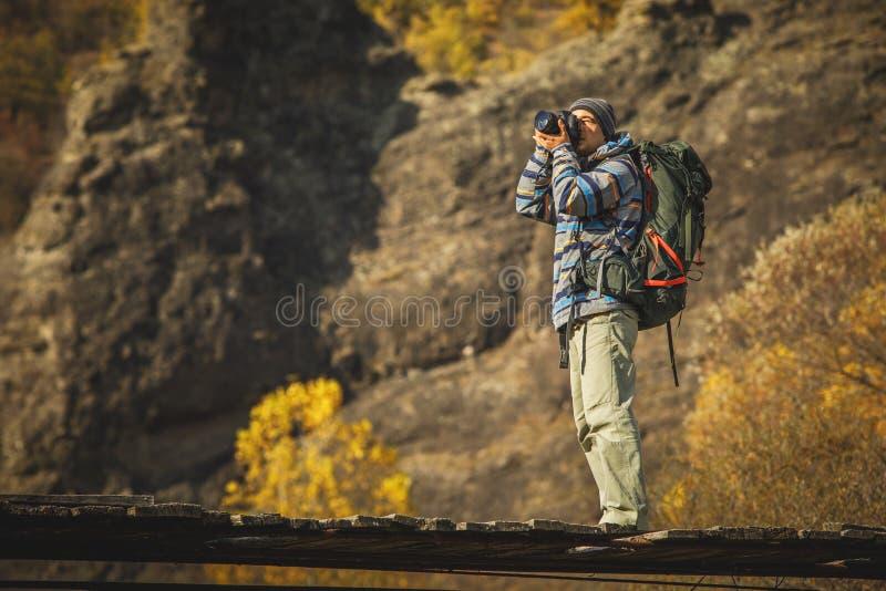 Équipez le photographe avec le grand sac à dos et l'appareil-photo prenant la photo du su image stock