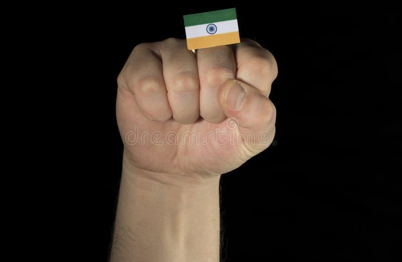 Équipez le poing de main avec le drapeau indien d'isolement sur le fond noir photos libres de droits