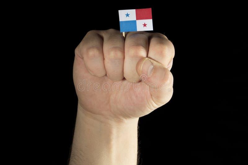 Équipez le poing de main avec le drapeau panaméen d'isolement sur le noir photo libre de droits