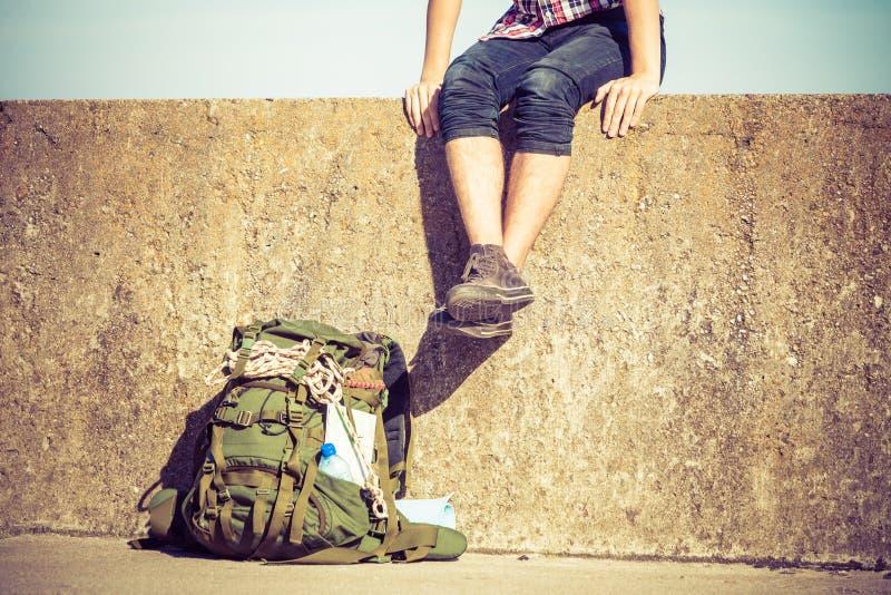 Équipez le randonneur de touristes s'asseyant sur le mur grunge extérieur image stock