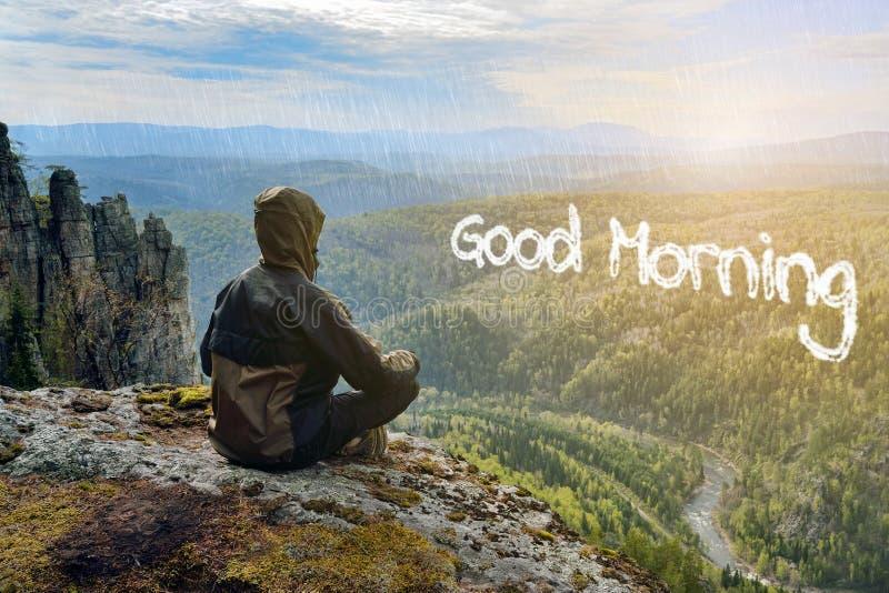 Équipez le randonneur s'asseyant sur le lever de soleil de réunion de montagne, lettrage bonjour sous la forme de nuages images libres de droits