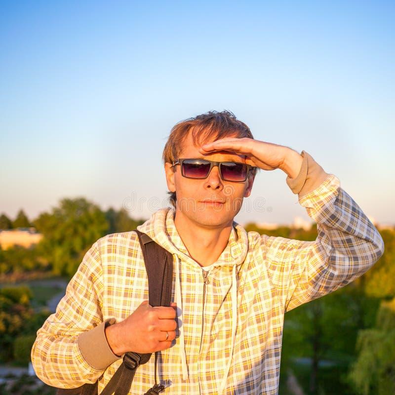 Équipez le randonneur tenant le sac à dos et regardant le coucher du soleil photos stock