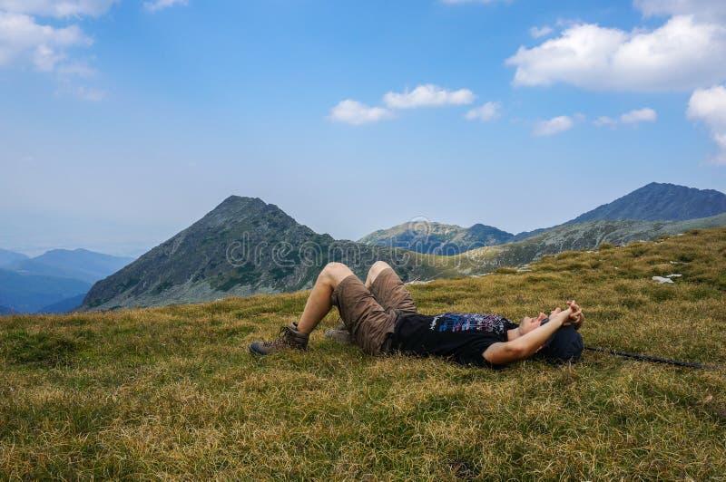 Équipez le repos sur l'herbe dans les montagnes photographie stock libre de droits