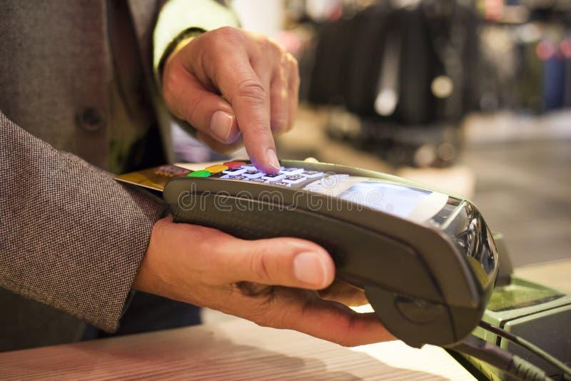 Équipez le salaire par la carte de crédit dans le magasin d'habillement images libres de droits