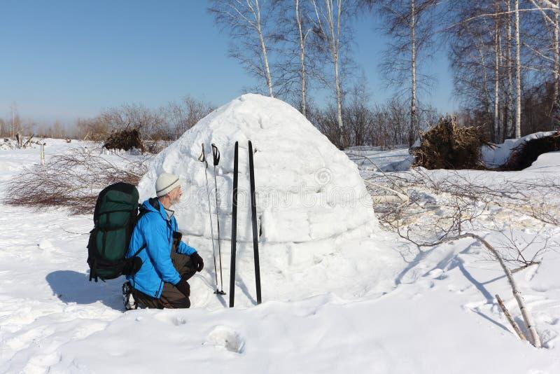 Équipez le skieur s'asseyant par un igloo sur une clairière pendant l'hiver photos libres de droits